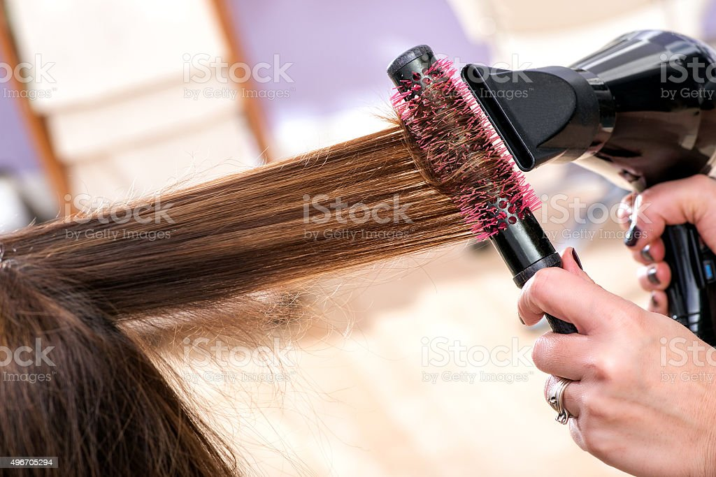 Hairdresser blow drying long brown hair stock photo