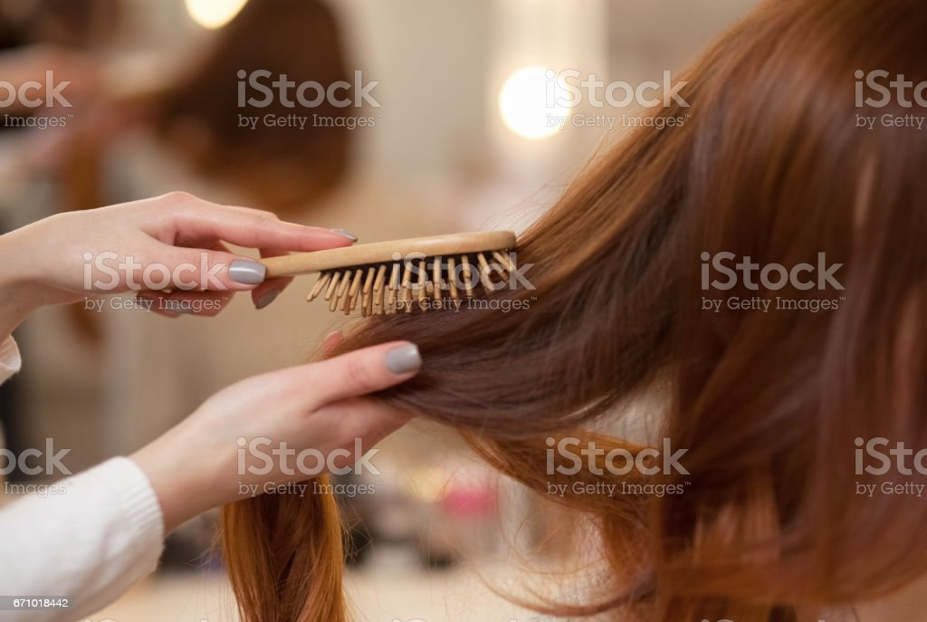 Hairdresser combing her long, red hair of his client in the beauty salon. stock photo