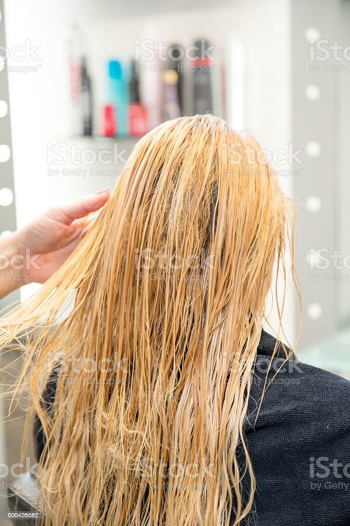 Hairdresser Combing Long Wet Blonde Hair In Hair Salon Stock Photo