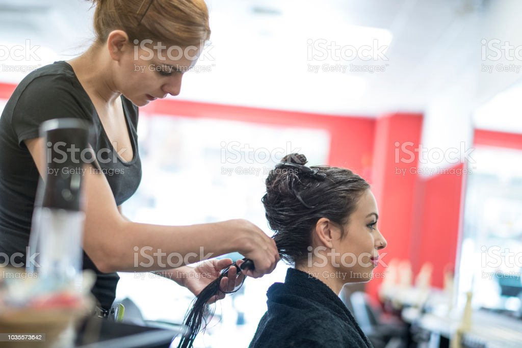 Hairdresser combing other woman hair stock photo
