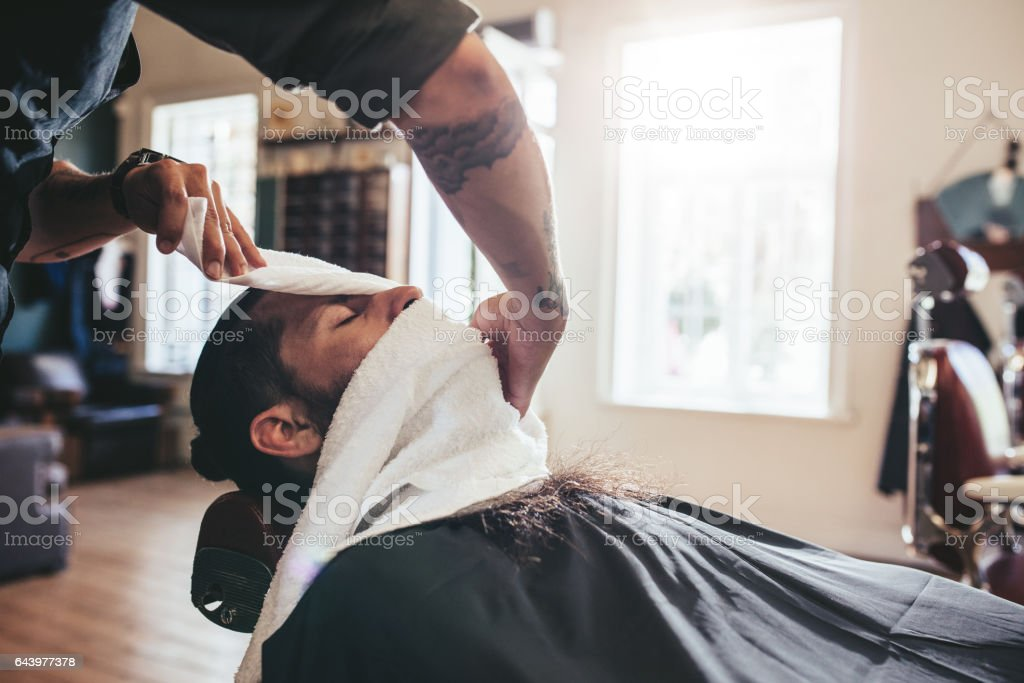 Hairdresser covering face of client with towel stock photo