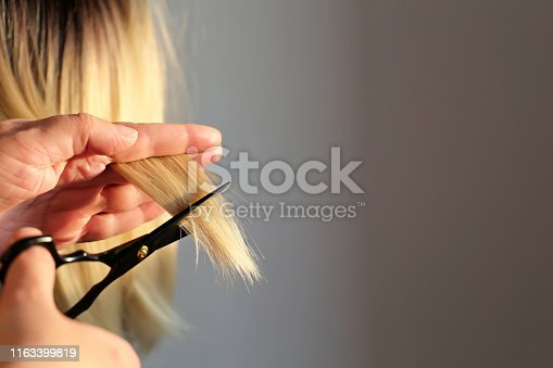 Scissors in female hands close up