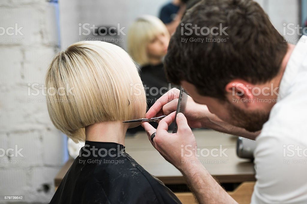 Hairdresser cutting client's hair in salon with electric razor stock photo
