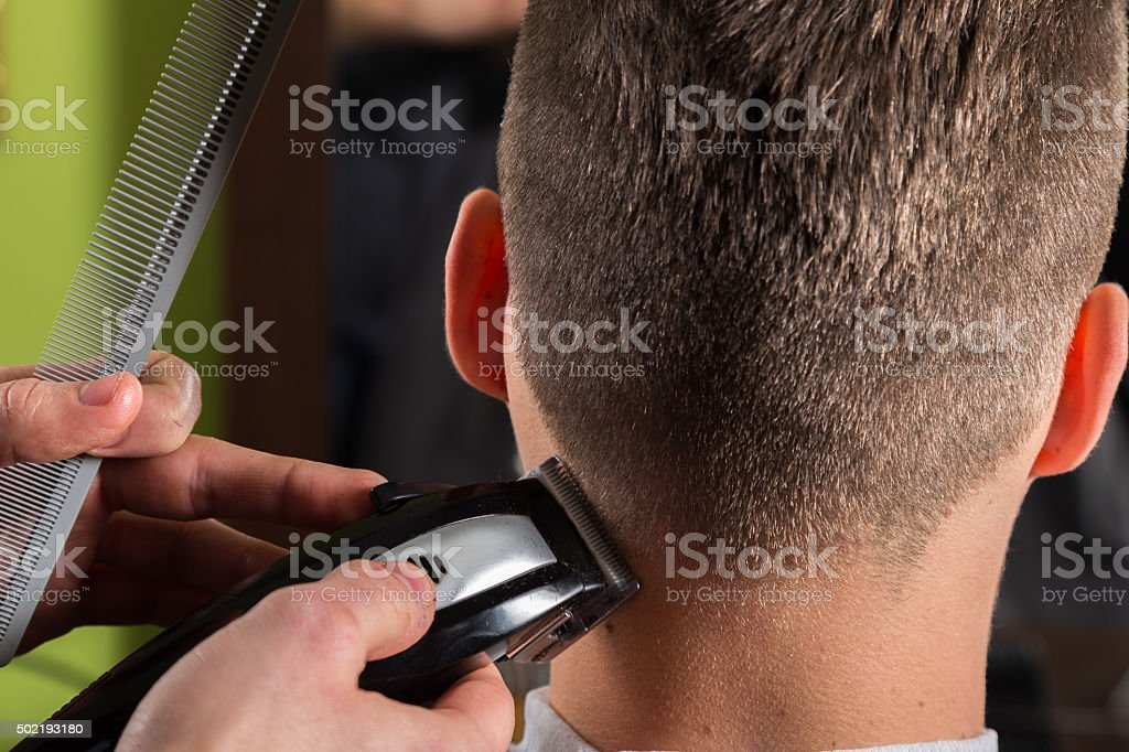 Hairdresser cutting clients hair with an electric hair clipper stock photo