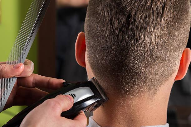 friseur schneiden kunden haar mit elektrischem hair clipper - männerfrisuren stock-fotos und bilder