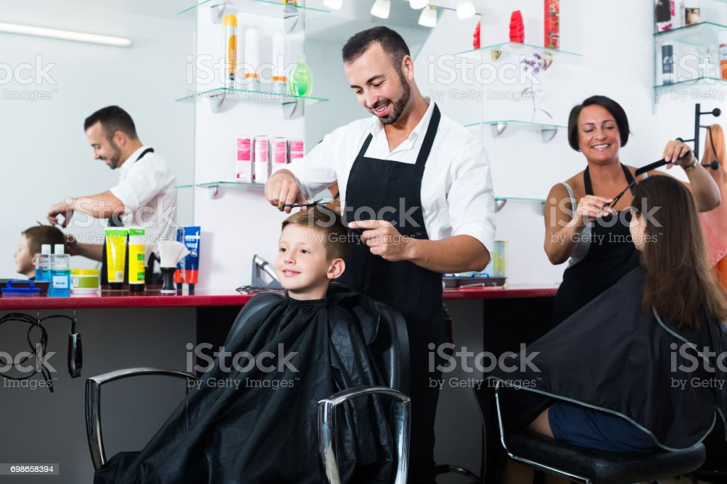 hairdresser cutting hair of boy in salon stock photo