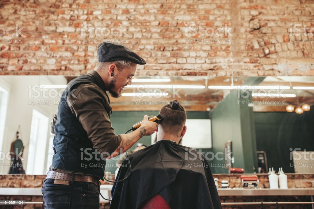 Hairdresser cutting hair of client stock photo