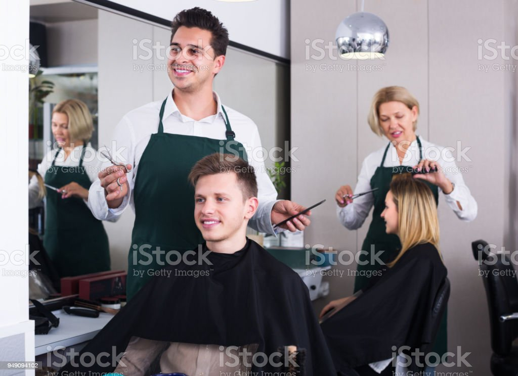 Hairdresser cutting hair of teenage stock photo