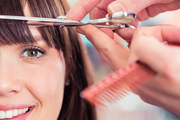 coiffeur coupe de cheveux frange femme dans la boutique - couper les cheveux photos et images de collection