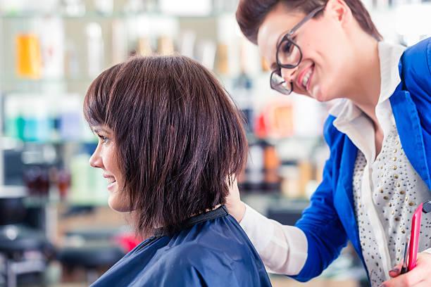 hairdresser cutting woman hair in shop - kurzhaarfrisuren mit pony stock-fotos und bilder