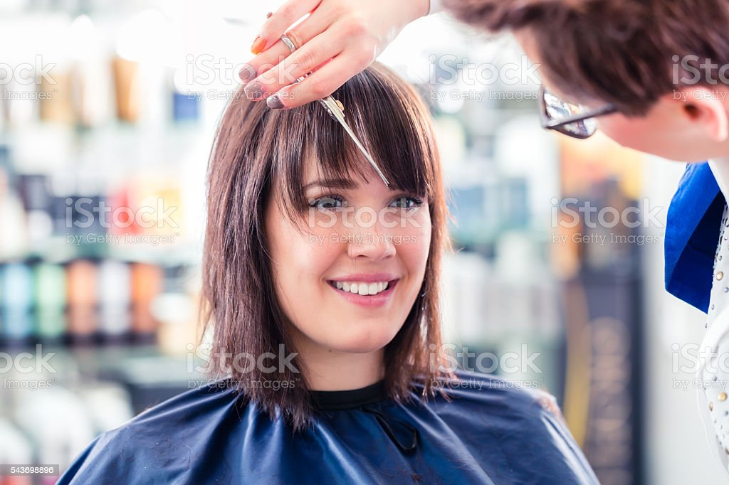 Hairdresser cutting woman hair in shop – Foto