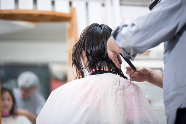 若い女性の髪をカット美容師 - 美容室 ストックフォトと画像