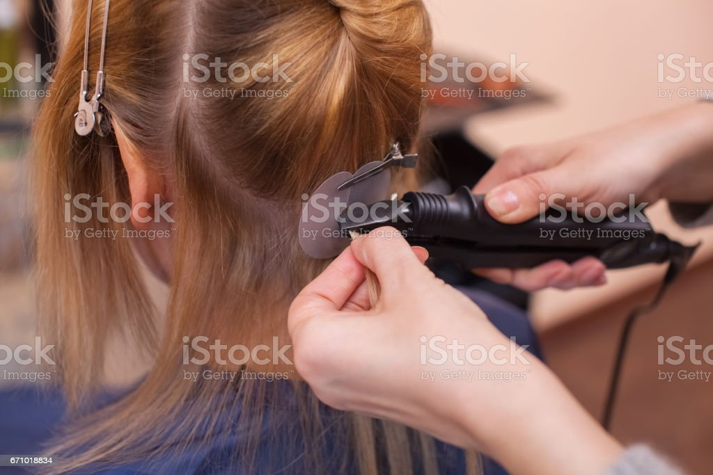hairdresser does hair extensions to a young girl, a blonde in a beauty salon stock photo