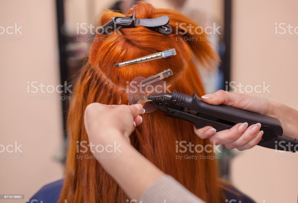 hairdresser does hair extensions to a young, red-haired girl, in a beauty salon stock photo