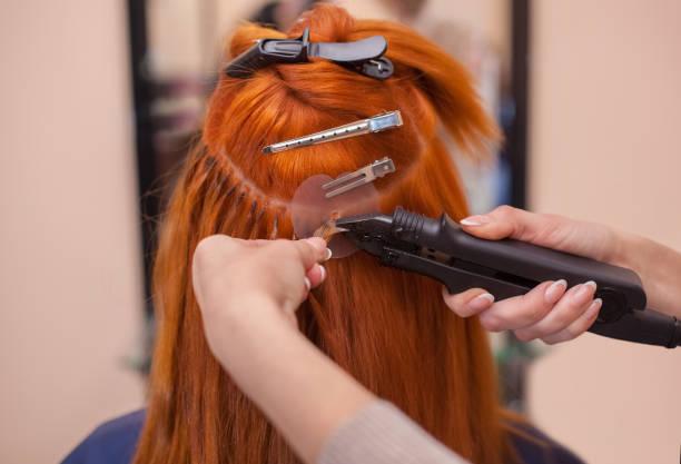 friseur tut haarverlängerung, um junge, rothaarige mädchen, in einem schönheitssalon - haarverlängerung stock-fotos und bilder