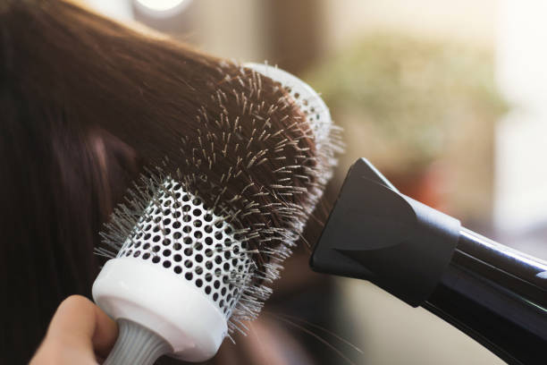 Hairdresser drying woman's hair in beauty salon Hairdresser drying woman's hair with hair dryer and round brush in beauty salon, closeup hairbrush stock pictures, royalty-free photos & images