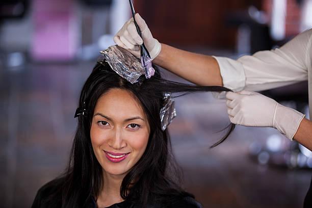 hairdresser dyeing hair of her client - folien highlights stock-fotos und bilder