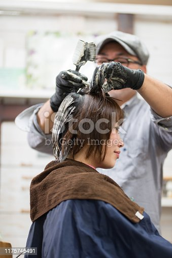 Hairdresser dyeing woman's hair brown