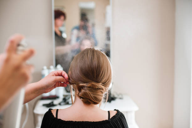 Hairdresser fixing woman hair with hairspray stock photo