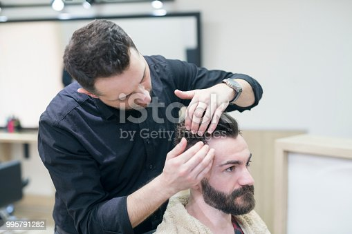 Hairdresser making stylish haircut