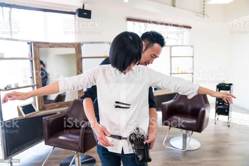 Hairdresser giving tools to new staff at a hair salon stock photo