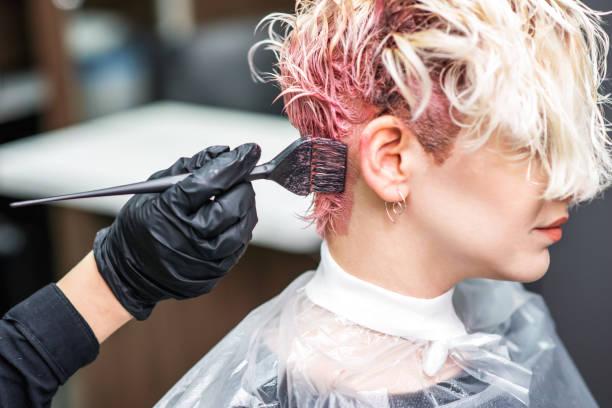 kapper hand in zwarte handschoenen schildert het haar van de vrouw in een roze kleur. - gekleurd haar stockfoto's en -beelden