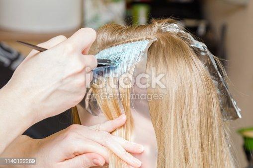 istock Hairdresser hands bleaching strands of blonde woman hair in beauty salon. Closeup. 1140122269