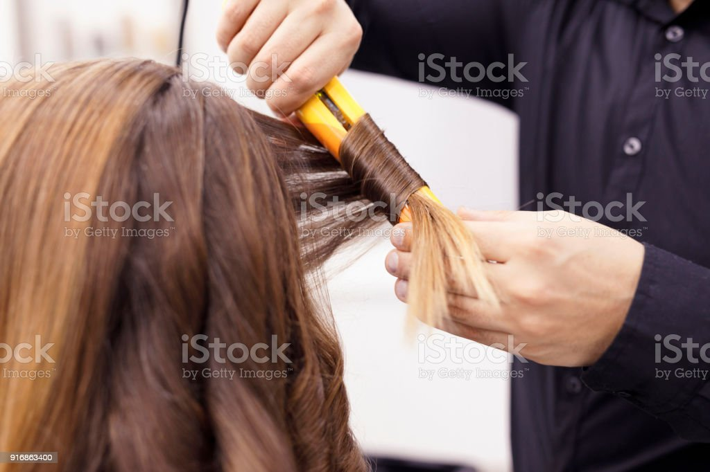 Hairdresser In Action Drying Long Hair Hair Curled With Flat Iron ... 5eeba625a4