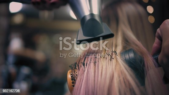 istock Hairdresser is strighten woman's long pink blonde hair with hair dryer and round professional hairbrush. Bottom view 932162706
