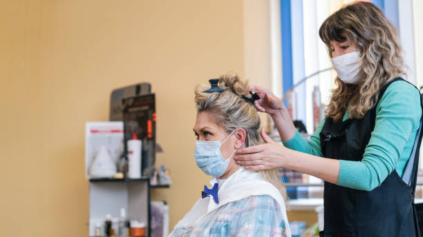 Hairdresser makes beautiful hairstyle, during COVID-19 stock photo