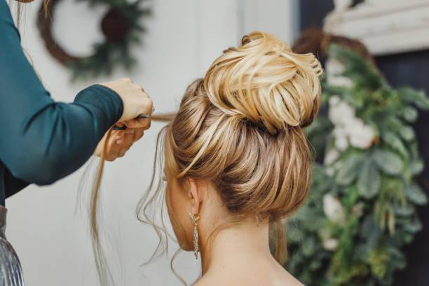 Friseur macht komplexe und schöne Frisur Oberbun. Geeignet für Abend und Hochzeit – Foto