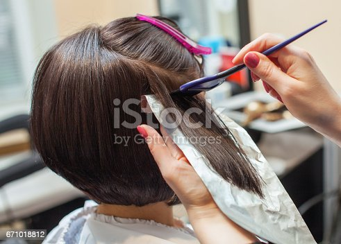 istock hairdresser paints the woman's hair in a dark color, apply the paint to her hair 671018812