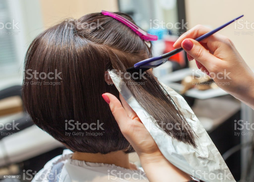 hairdresser paints the woman's hair in a dark color, apply the paint to her hair stock photo