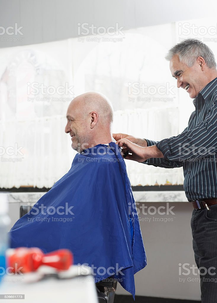 Hairdresser Removing Cape From Senior Man stock photo