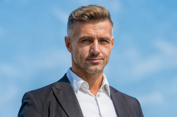 Hairdresser salon. Stylish hairstyle. Male face. Businessman concept. Facial care and ageing. Attractive mature man. Mature guy with grey hair and bristle outdoors. Men get more attractive with age stock photo