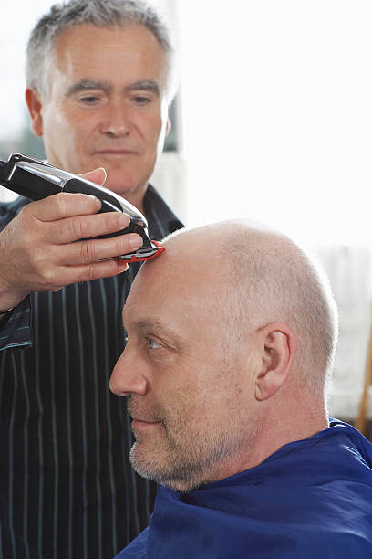 männliche friseur rasieren kunde's head - glatze schneiden stock-fotos und bilder