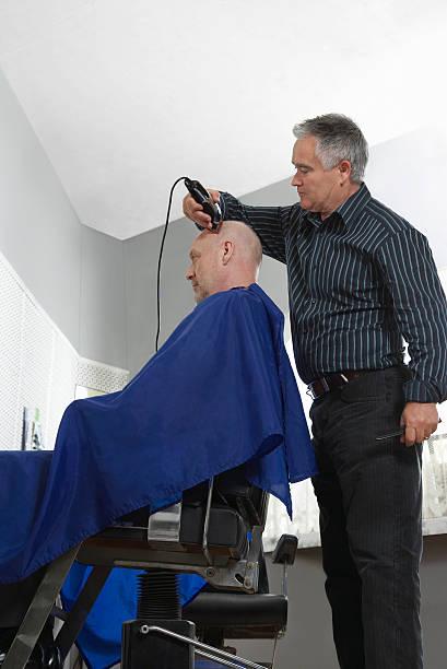 friseur rasieren mann's head mit elektrorasierer - glatze schneiden stock-fotos und bilder