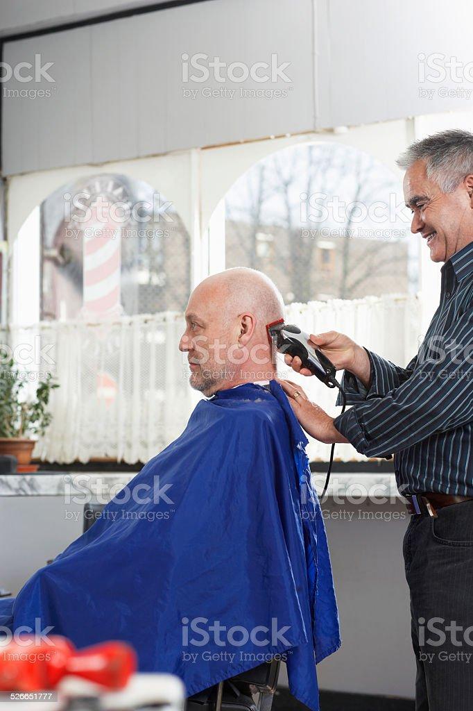 Hairdresser Shaving Man's Head With Electric Razor stock photo