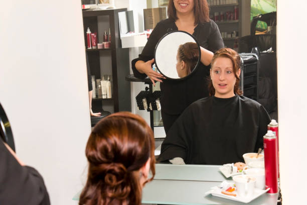 Hairdresser shows hairstyle with a mirror stock photo