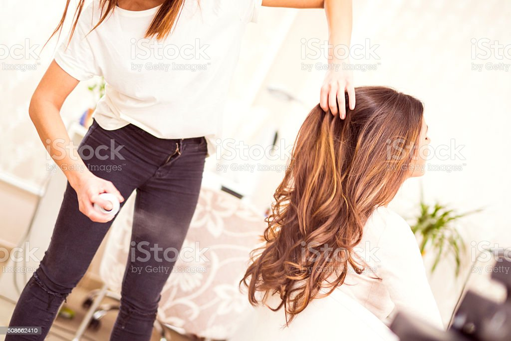 Hairdresser spraying his customer's hair stock photo