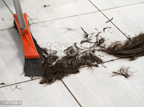 Hairdresser sweeping hair clippings on floor in barber shop.