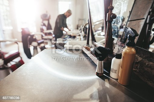 istock Hairdresser tools on counter at barber shop 637785236
