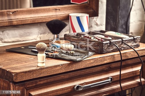 istock Hairdresser tools on wooden background. Top view on wooden table with scissors, comb, hairbrushes and hairclips, trimmer. 1137576245