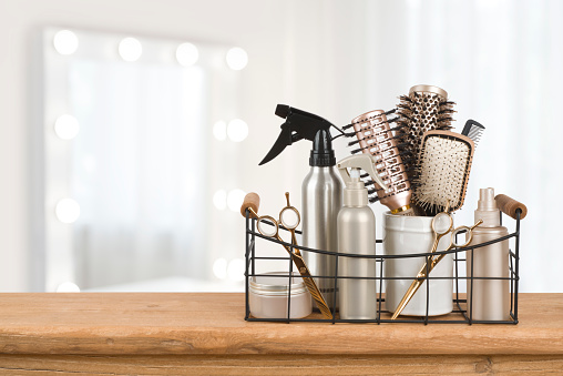 Hairdresser tools on wooden table with blurred beauty salon background