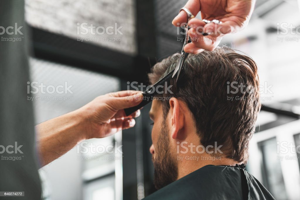 Hairdresser undergoing hairdo at salon stock photo