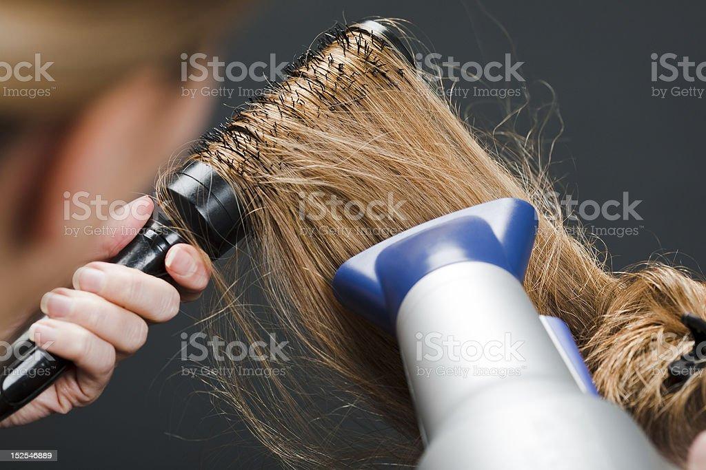 Hairdresser using hairbrush and hair dryer stock photo