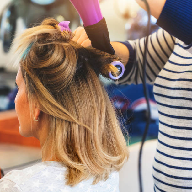 Hairdresser using hairbrush and hair dryer Female hairdresser using hairbrush and hair dryer highlights hair stock pictures, royalty-free photos & images
