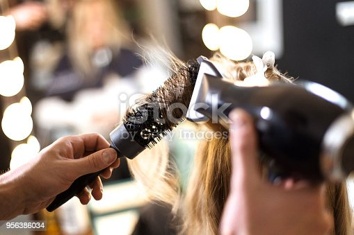 Hairdresser using hairdryer watching not to dry to much