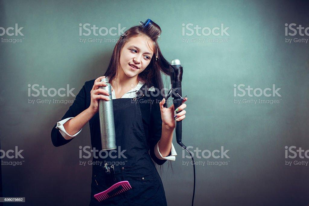 Hairdresser using hairspray on hair at salon stock photo