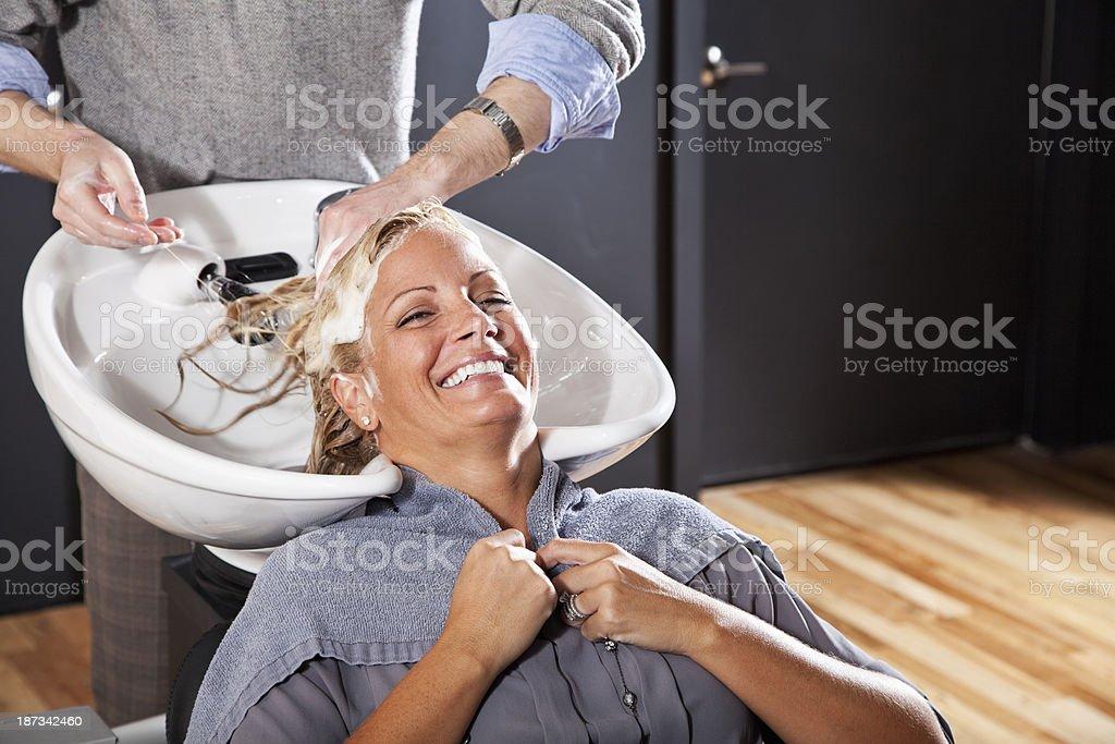 Hairdresser washing customer's hair royalty-free stock photo